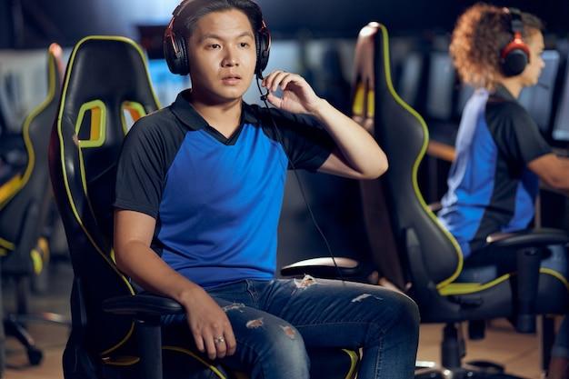 Mislukkingsportret van een aziatische mannelijke cybersport-gamer die een koptelefoon draagt en naar het pc-scherm kijkt