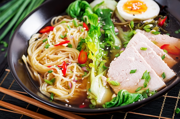 Miso ramen aziatische noedels met ei, varkensvlees en pak choikool in kom op donkere oppervlakte.
