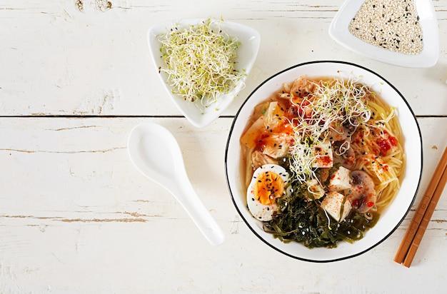 Miso ramen aziatische noedels met koolkimchi, zeewier, ei, paddestoelen en kaastofu in kom op witte houten lijst.