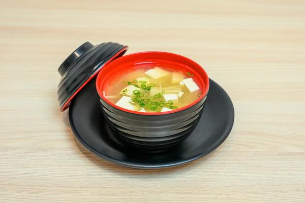 Misosoep met tofu en groente in zwarte kop met deksel
