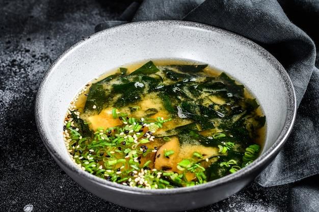 Misosoep met tofu en zeewier. zwarte achtergrond. bovenaanzicht
