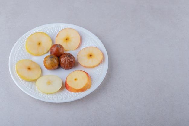Mispel en gesneden appels op plaat op marmeren tafel.