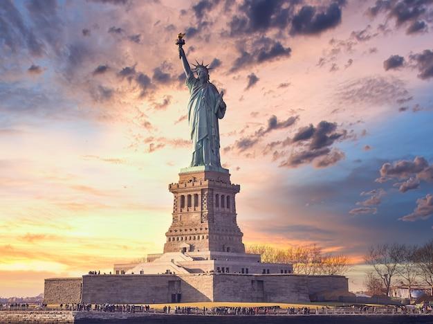 Miss vrijheid bij zonsondergang in de stad new york, verenigde staten