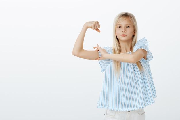 Misschien ben ik klein maar sterk. portret van trots zelfverzekerd jong blond meisje in stijlvolle blouse, hand opsteken en spieren tonen, praten over kracht, zelfverzekerd en tevreden voelen over grijze muur