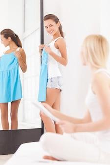 Misschien deze jurk? mooie jonge vrouw die in de buurt van de spiegel staat met blauwe jurk en kijkt naar een andere vrouw die op de voorgrond zit met tijdschrift