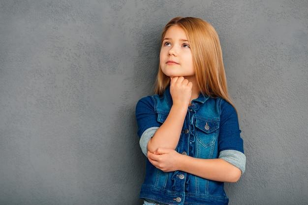 Misschien is dit een goed idee? mooi klein meisje houdt hand op kin en kijkt weg terwijl ze tegen een grijze achtergrond staat