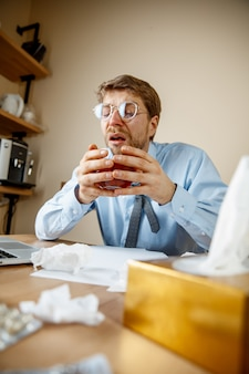 Misselijk en moe voelen. de man met een kopje hete thee op kantoor werken