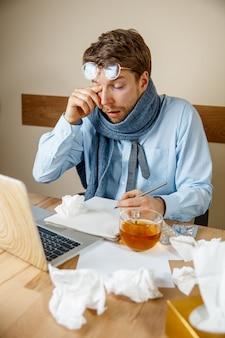 Misselijk en moe voelen. gefrustreerd triest ongelukkig zieke jongeman zijn ogen masseren