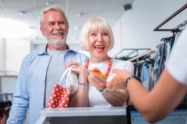 Missie gedaan. opgetogen stijlvolle bejaarde echtpaar staat voor de kassa terwijl ze een betaalkaart doorgeven aan de verkoopster