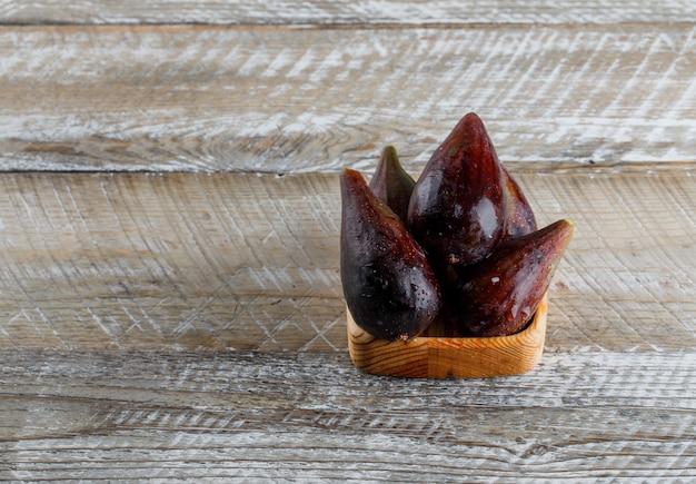 Mission vijgen in een stuk hout op een houten tafel. hoge hoekmening. ruimte voor tekst