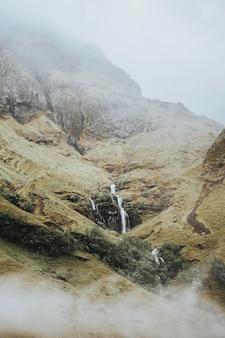 Mist bedekt een smalle waterval in schotland