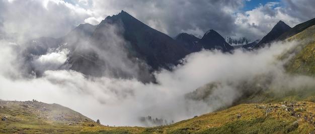 Mist in de vallei en wolken op de toppen. berg, altai. panoramisch zicht.