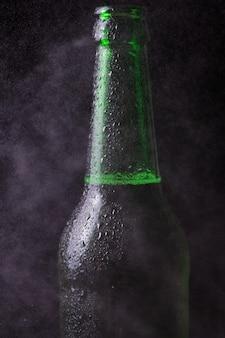 Misted koude fles bier in de mist van waterdruppels op een zwarte achtergrond.