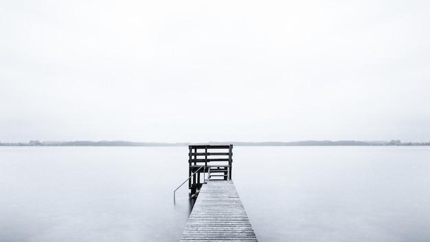 Mistig landschap van een pier die leidt naar de oceaan op een koude ochtend