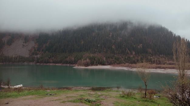 Mistig meer in de bergen van kazachstan