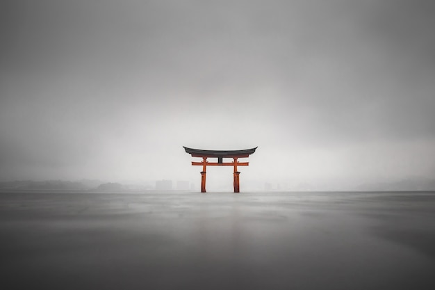 Mistig schot van de drijvende torii van miyajima, japan tijdens regen