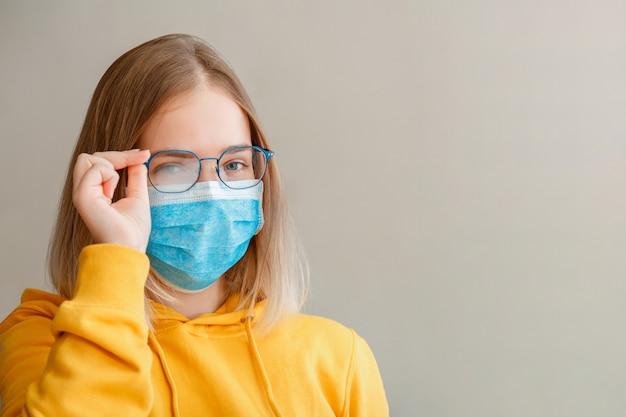 Mistige bril dragen op jonge vrouw. tienermeisje in blauw medisch beschermend gezichtsmasker en bril veegt wazig mistige beslagen bril af met kopieerruimte. nieuw normaal.
