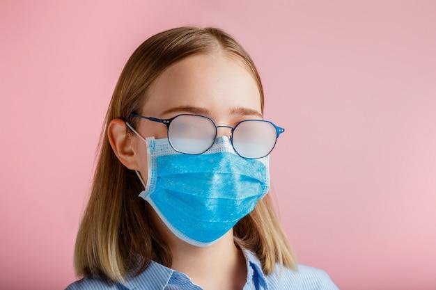 Mistige bril dragen op jonge vrouw. tienermeisje met medisch beschermend gezichtsmasker en bril veegt wazig mistige beslagen bril op roze kleur muur. nieuwe normale covid coronavirusvergrendeling.