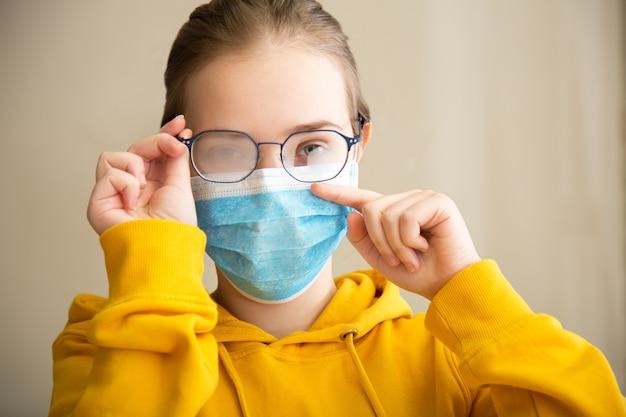 Mistige bril dragen op jonge vrouw. tienermeisje met medisch beschermend gezichtsmasker en bril veegt wazig mistige beslagen glazen af. nieuwe normaal door covid coronavirus.