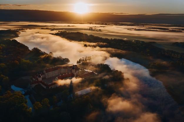 Mistige dageraad in nesvizh. uitzicht vanaf de hoogte van het kasteel van nesvizh en het park bij zonsopgang.