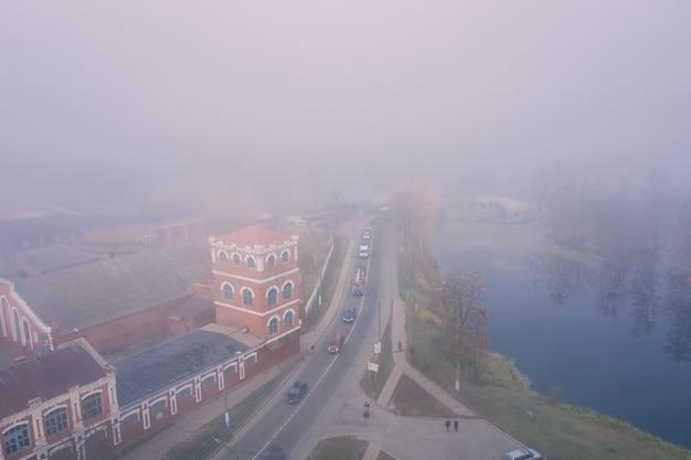 Mistige ochtend in een klein stadje met uitzicht op de weg en de oude papierfabriek