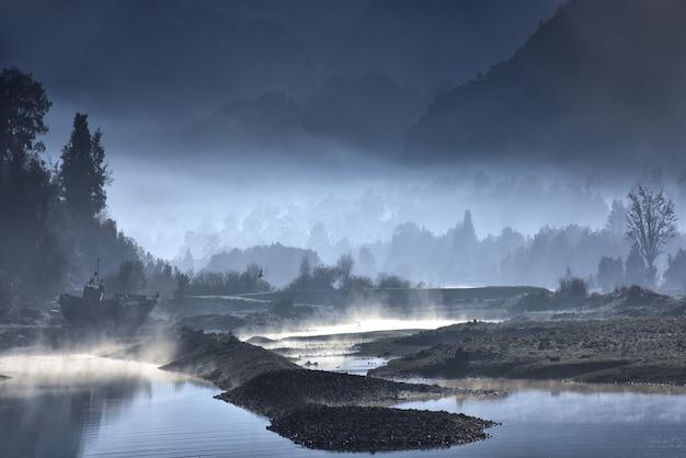 Mistige oever van een meer met bossen 's nachts