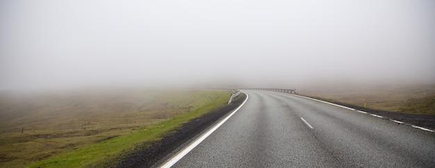 Mistige weg. gevaarlijke en mystieke mistige snelweg