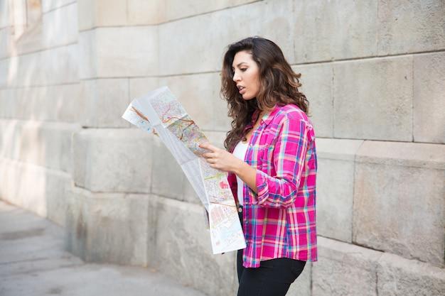 Misverstand meisje kijken naar de kaart van de stad
