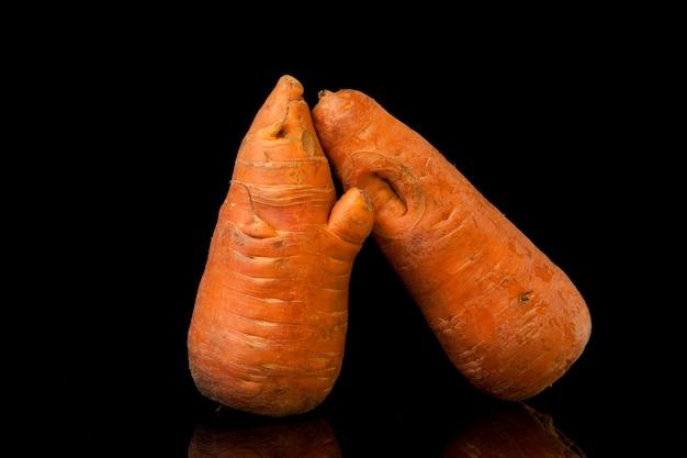 Misvormde biologische wortelen op zwarte achtergrond. misvormde producten, voedselverspilling probleem concept.