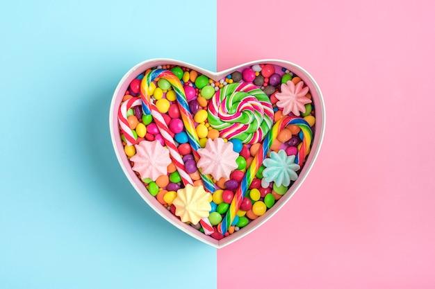 Mix chocolade snoepjes liggen in geschenkdoos vorm van hart op kleurrijke achtergrond