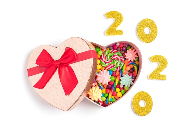 Mix kleurrijke chocolade snoepjes liggen in geschenkdoos vorm van hart geïsoleerd wit plat lag