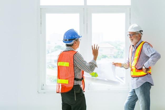 Mix race senior bouwingenieur werknemer praten samen over de toekomst van design met blauwdruk