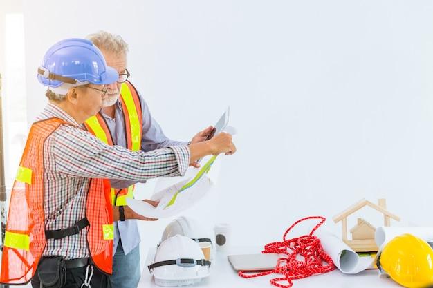 Mix race senior bouwingenieurs werken samen op zoek naar blauwdruk en discussie.