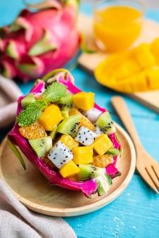 Mix tropische fruitsalade geserveerd in een half drakenfruit op houten tafel