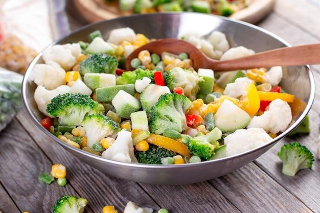 Mix van bevroren groenten in een kom op houten tafel