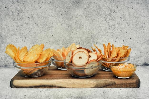 Mix van chips, snacks en crackers op een houten standaard. ongezond voedsel, biersnack, kant-en-klaarmaaltijd. detailopname
