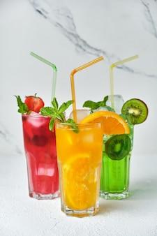Mix van drie felgekleurde heerlijke koude limonadekaraffen van kiwi en sinaasappel en aardbei met munt op lichte ondergrond