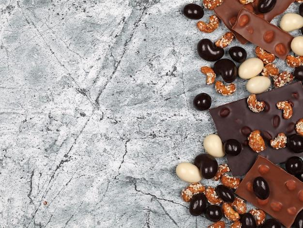 Mix van gebroken chocoladerepen, zoete cashewnoten en met chocolade bedekte noten op grijze stenen achtergrond
