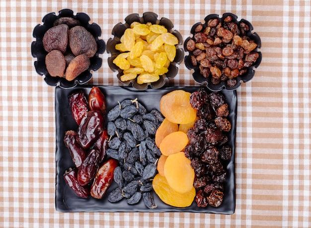 Mix van gedroogde vruchten dadels rozijnen abrikozen en kersen op een zwart dienblad en in mini taartvormpjes op geruite tafelkleed bovenaanzicht