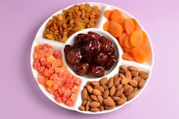 Mix van gedroogde vruchten en noten op een witte plaat. abrikoos, amandel, rozijnen, dadels fruit. op een lila achtergrond. ruimte voor tekst of ontwerp.