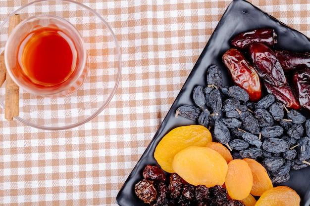 Mix van gedroogde vruchten, kersen, abrikozen, zwarte rozijnen en dadels op een zwart dienblad, geserveerd met armudu glas thee op geruite tafelkleed bovenaanzicht