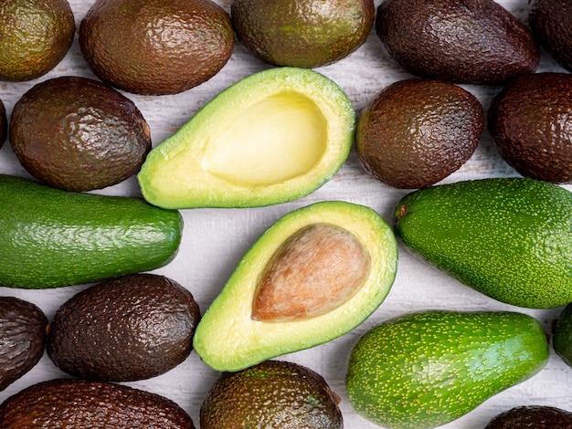 Mix van gescheurde en groene avocado's op een wit houten bord.