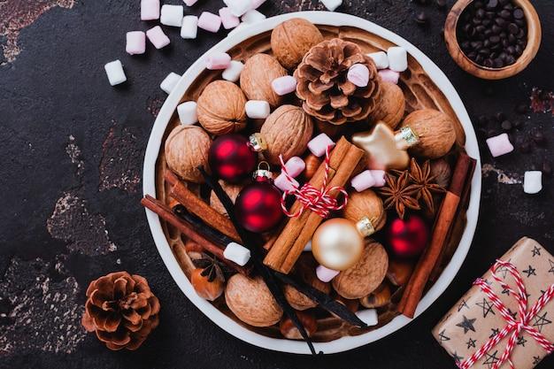 Mix van gezonde rauwe hazelnoten en walnoten, kaneelstokjes, anijs, vanille, chocolade en kerstmisspeelgoed in keramische plaat op bruin betonnen oppervlak