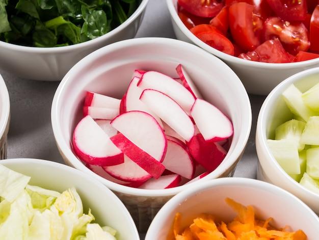 Mix van groentekommen voor salade of snacks op grijs