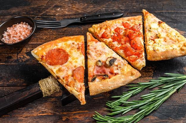Mix van italiaanse pizza op een houten snijplank. donkere achtergrond. bovenaanzicht.