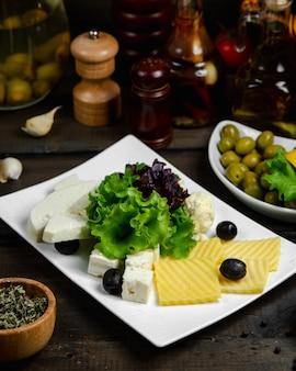 Mix van kaas geserveerd met basilicum en olijven