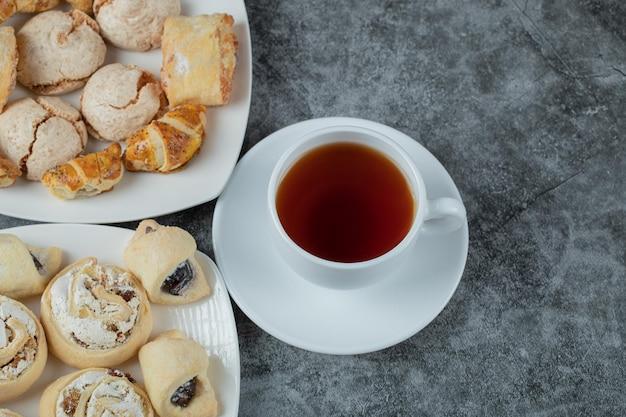 Mix van koekjes op schotel geserveerd met een kopje earl grey thee.