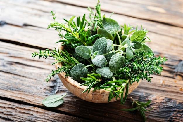 Mix van kruiden: salie, tijm, rozemarijn op de houten tafel, selectieve aandacht