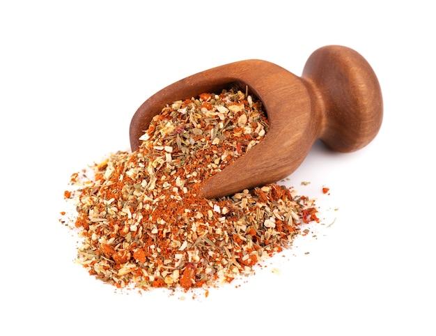Mix van kruiden, specerijen en droge tomaten in houten lepel, geïsoleerd op wit