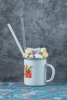 Mix van marshmallow en jellybeans in een blauwe metalen beker.